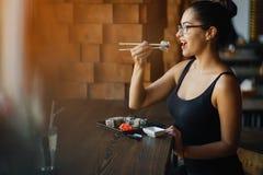 吃寿司的女孩在餐馆 免版税库存照片