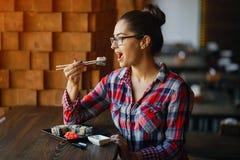 吃寿司的女孩在餐馆 免版税库存图片