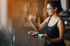 吃寿司的女孩在餐馆 库存照片