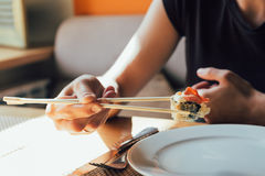 吃寿司的女孩在餐馆 免版税图库摄影