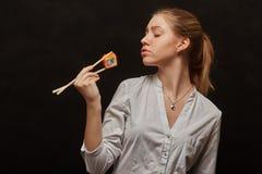 吃寿司的女孩 免版税库存照片