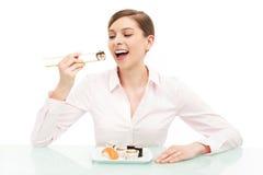 吃寿司的美丽的妇女 免版税库存照片