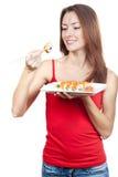 吃寿司的美丽的深色的妇女 免版税库存照片