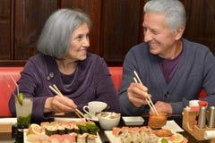吃寿司的年长夫妇 免版税库存图片
