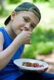 吃小的草莓的男孩通配 图库摄影
