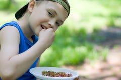 吃小的草莓的男孩通配 库存照片