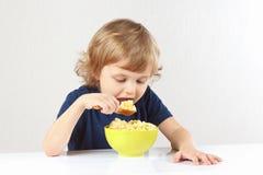 吃小米粥的美丽的白肤金发的子项 免版税库存照片