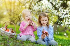 吃巧克力兔宝宝的两个可爱的妹在春天庭院里在复活节天 免版税库存照片