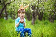 吃巧克力和佩带复活节兔子耳朵的愉快的矮小的小孩男孩,在开花的庭院里坐温暖的晴天 庆祝 库存照片