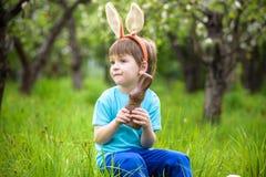 吃巧克力和佩带复活节兔子耳朵的愉快的矮小的小孩男孩,在开花的庭院里坐温暖的晴天 庆祝 免版税库存图片