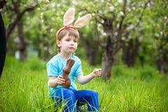 吃巧克力和佩带复活节小圆面包的愉快的矮小的小孩男孩 免版税图库摄影