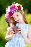 吃巧克力复活节兔子的逗人喜爱的小女孩佩带的花花圈 免版税库存图片