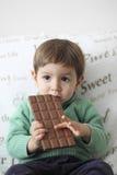 吃巧克力片剂的微笑的婴孩 库存照片