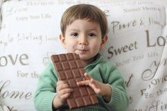 吃巧克力片剂的微笑的婴孩 免版税库存图片