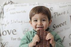 吃巧克力片剂的愉快的婴孩 库存图片