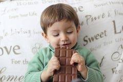 吃巧克力片剂的愉快的婴孩 库存照片