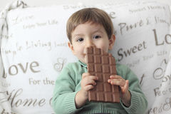吃巧克力片剂的婴孩 免版税库存照片