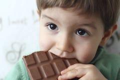 吃巧克力片剂的婴孩 库存图片