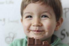 吃巧克力片剂的婴孩 免版税库存图片