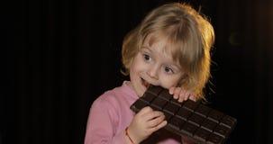 吃巧克力的一个巨大的块可爱的孩子 逗人喜爱的白肤金发的女孩 免版税库存照片