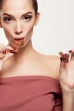 吃巧克力的可爱的微笑的十几岁的女孩 免版税库存图片