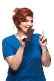 吃巧克力的弯曲的妇女 免版税库存图片