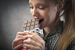 吃巧克力的白肤金发的女孩 免版税库存照片