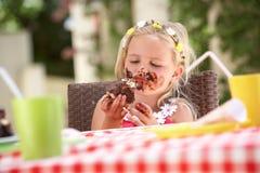 吃巧克力蛋糕的杂乱女孩 免版税库存图片