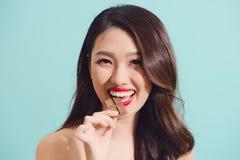 吃巧克力,特写镜头的可爱的年轻亚裔妇女 免版税库存照片