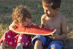 吃巨型切片成熟西瓜的女孩和男孩 免版税图库摄影