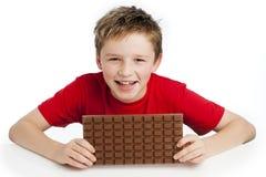 吃巨大的巧克力块的男孩 免版税图库摄影
