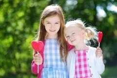 吃巨大的心形的棒棒糖的两个逗人喜爱的妹户外 库存图片