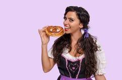 吃巴法力亚椒盐脆饼的逗人喜爱的微笑的女孩 库存图片