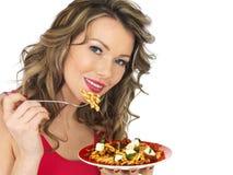 吃希腊白软干酪和蕃茄意大利面制色拉的少妇 免版税库存照片