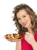 吃希腊白软干酪和Tommato意大利面制色拉的少妇 免版税库存图片