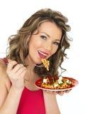 吃希腊白软干酪和Tommato意大利面制色拉的少妇 免版税库存照片