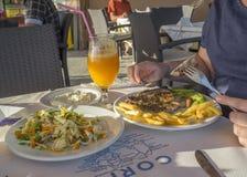 吃希腊膳食的妇女手在科孚岛的,与薯条和农夫沙拉,tzatziki的烤猪肉牛排希腊小酒馆 免版税库存图片