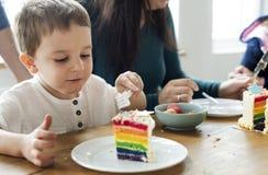 吃彩虹色的蛋糕的小男孩 免版税库存图片