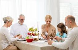 吃微笑的家庭假日晚餐在家 免版税图库摄影