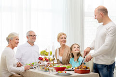吃微笑的家庭假日晚餐在家 免版税库存照片