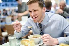 吃微笑的年轻的商人午餐 库存照片