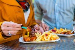 吃德国人Currywurst的夫妇 免版税库存图片