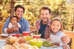 吃快乐男性的夫妇与女儿的室外午餐 库存图片