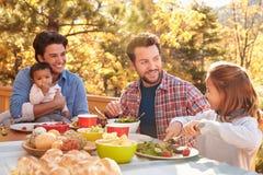 吃快乐男性的夫妇与女儿的室外午餐 免版税库存照片