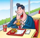 吃快餐乳酪汉堡的大人 免版税库存照片
