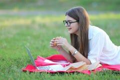 吃快餐和工作的本质的女孩在膝上型计算机 免版税库存图片
