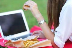 吃快餐和工作的本质的女孩在膝上型计算机 库存图片