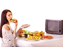 吃快餐和看电视的妇女。 免版税库存照片