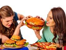 吃快餐的妇女 Gils吃汉堡包用火腿 免版税图库摄影