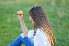 吃快餐的本质的女孩 图库摄影